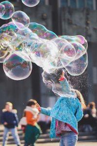 ребенок играет с большими мыльными пузырями