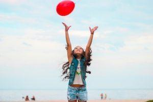 ребенок на пляже ловит воздушный красный шар