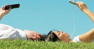 два человека лежат на траве с телефонами