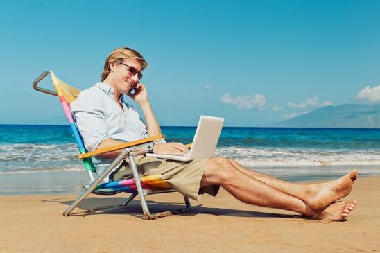 человек сидит на шезлонге с компьютером и телефоном