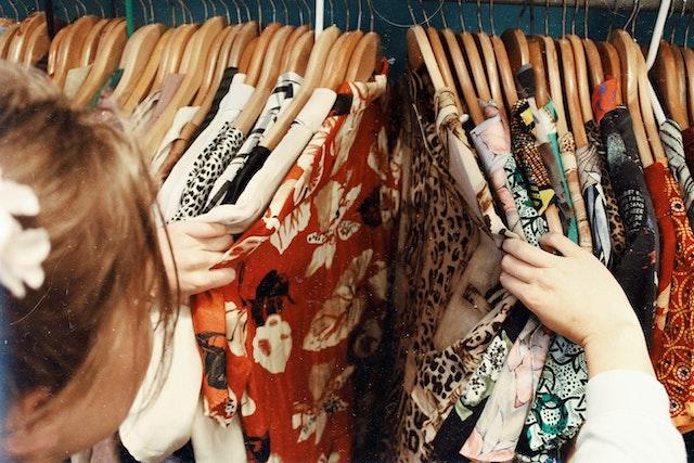 девушка смотрит одежду на вешалках