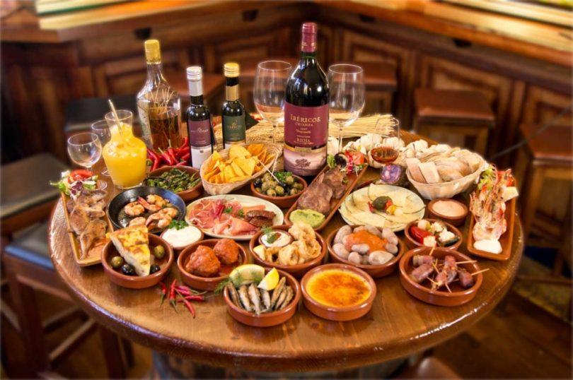 круглый стол, заваленный блюдами и напитками
