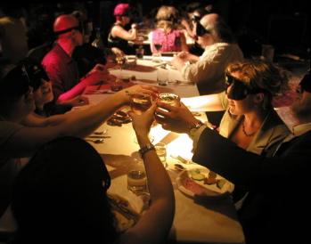 компания людей сидит за столом в темноте