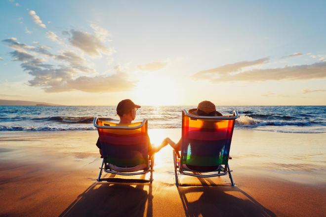 два человека сидят на столах у моря