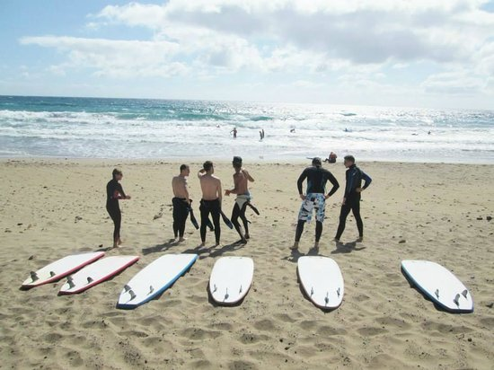 группа людей на берегу моря с досками для серфинга