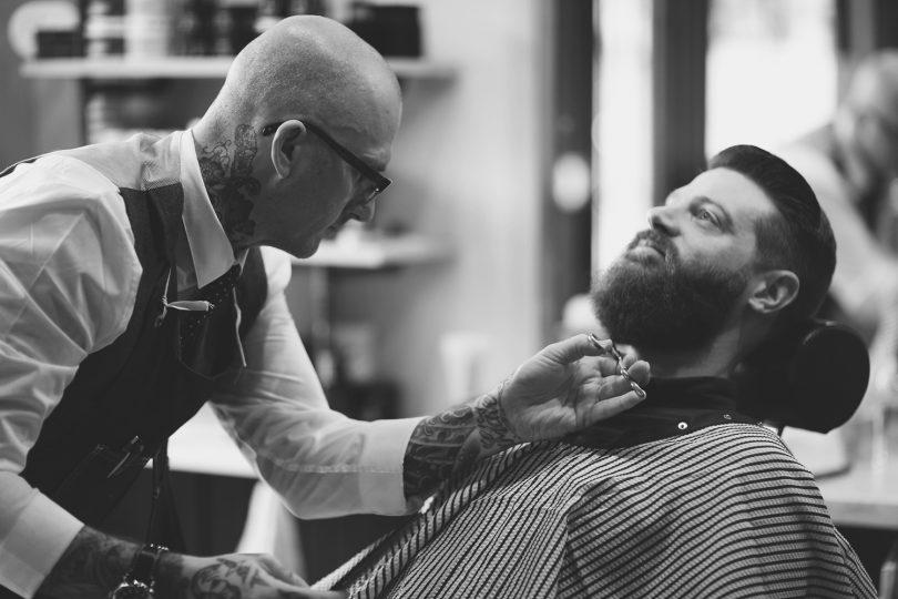 черно-белая фотография мастера с клиентом в барбер-шопе