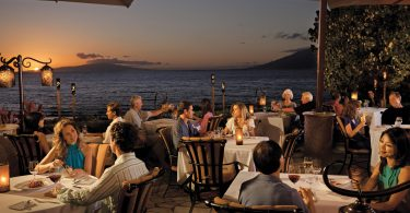 люди сидят за столиками в ресторане у моря