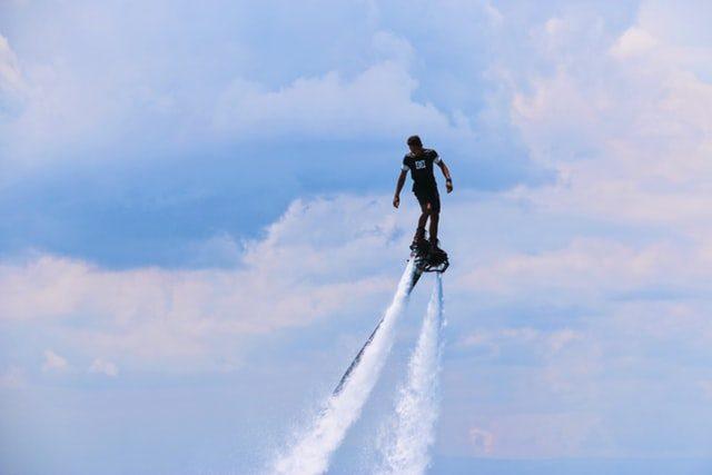 мужчина летит на флайборде