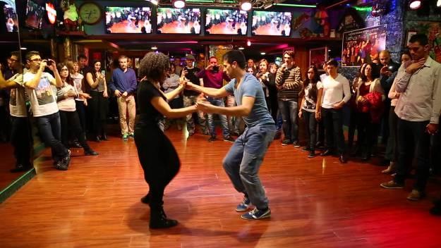 два человека танцуют сальсу в кругу людей