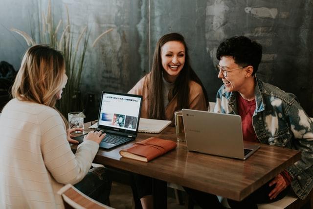 три девушки сидят за столом и смеются