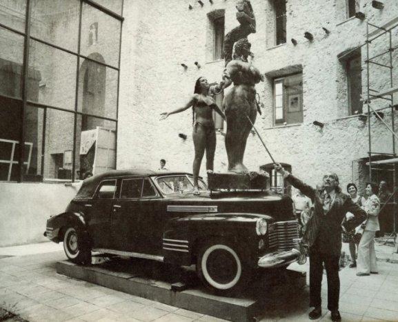 человек стоит у машины, на которой стоит женщина и скульптура
