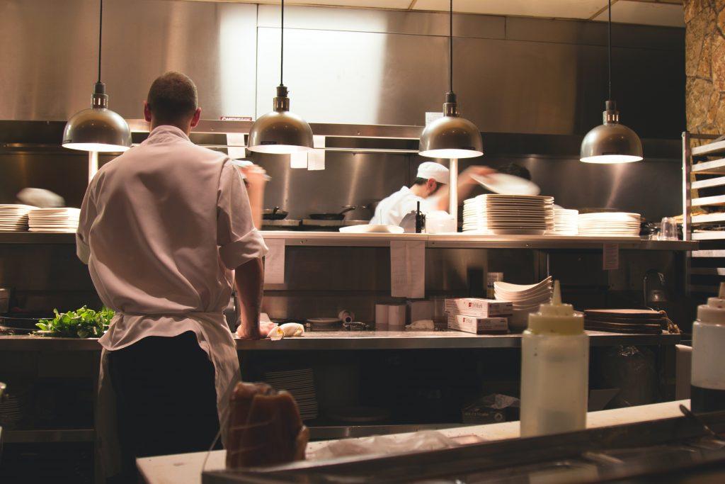 повар в белой форме на кухне