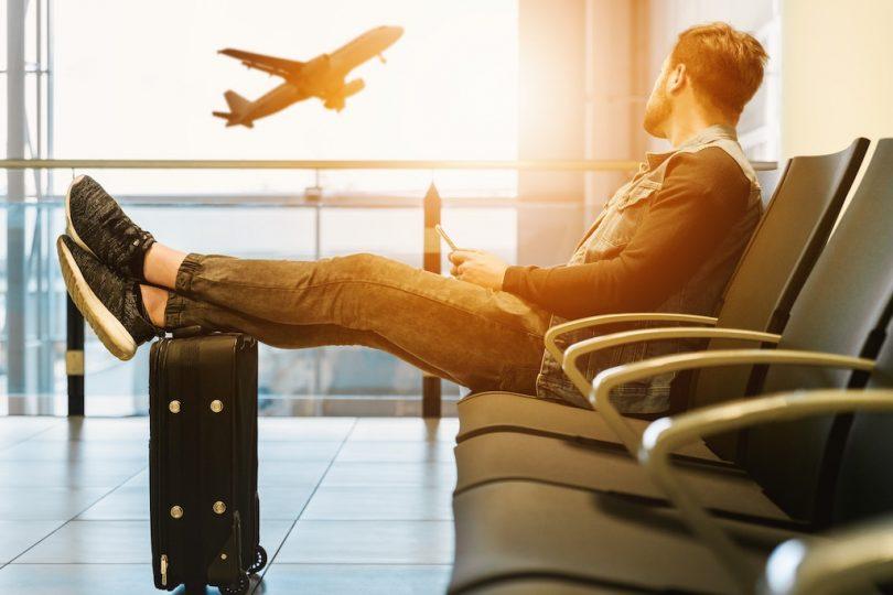 человек сидит в аэропорту и смотри на самолет