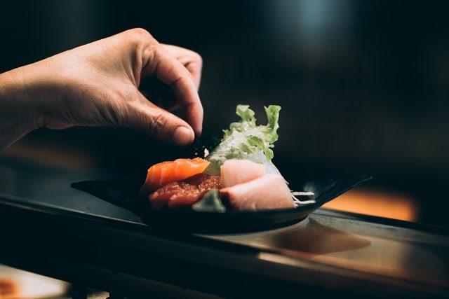 блюдо с суши и листьями салата