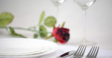 тарелка, вилки и роза на столе