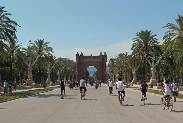 велосипедисты едут по дороге возле Триумфальной арки в Барселоне