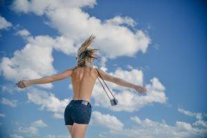 девушка с оголенным верхом на фоне неба