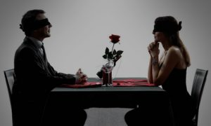 две человека сидят друг против друга с завязанными глазами