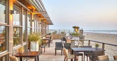 терраса со стульями и столами на берегу моря