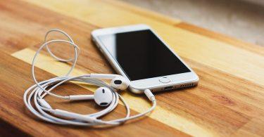 белый телефон с наушниками на столе