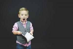 удивленный ребенок с книгой в руке