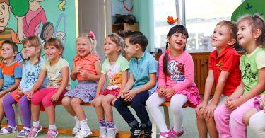 дети сидят в ряду и улыбаются