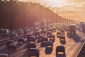 машины едут по дороге при закате
