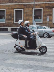 два человека в шлемах едут на скутере