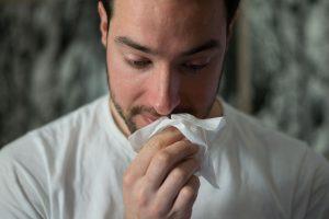 мужчна держит белые платок у носа