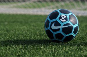 футбольный мяч с синими вставками на траве