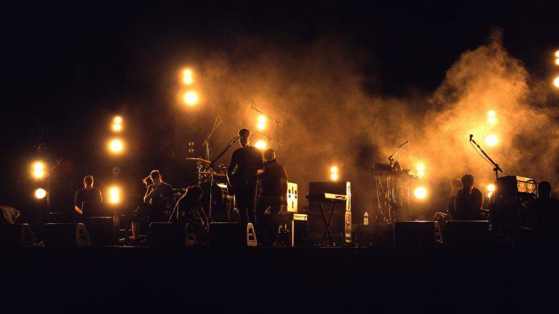 сцена, на которой горят огни и видны силуэты