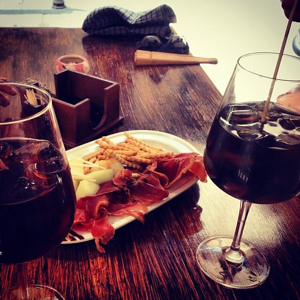 два бокала вина и блюдо с хамоном и сыром