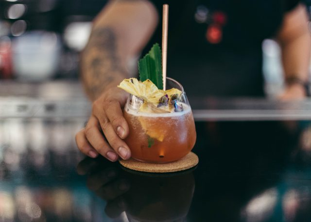 бокал напитка с ананасом на барной стойке