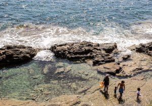люди стоят на камнях у воды