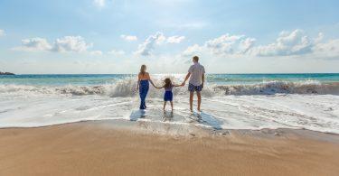 семья держится за руки стоя лицом к морю