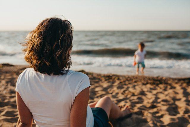 женщина лежит на пляже и смотрит на сына у моря