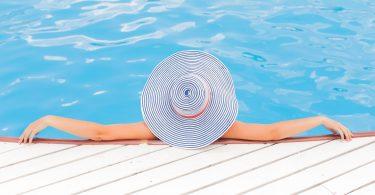 Женщина в шляпе отдыхает в бассейне