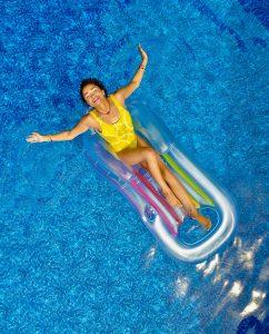 девушка на матрасе купается в бассейне