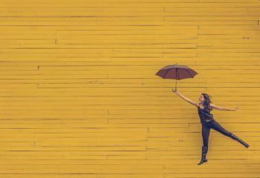 женщина с зонтиком на жёлтом фоне