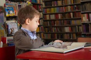 ребёнок читает книгу в библиотеке