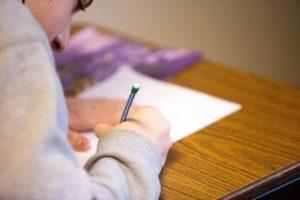 ребёнок пишет карандашом на белом листе