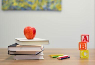 яблоко, кубики, книги и карандаши на парте