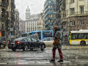 девушка переходит улицу Барселоны во время снегопада
