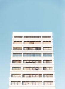 многоэтажный белый дом на фоне голубого неба
