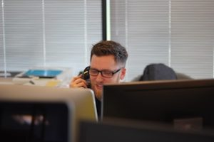 мужчина сидит за письменным столом с двумя экранами