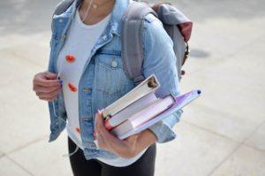 девушка в наушниках с книжками в руках