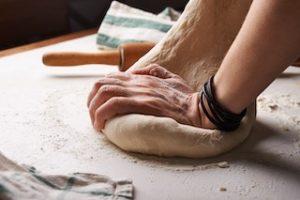 руки разминают тесто