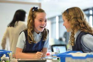 две девочки в школьной форме разговаривают
