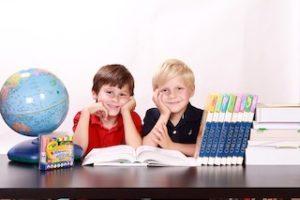 два мальчика сидят в классной комнате с книжками и глобусом
