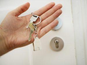 ключи в руке напротив белой двери
